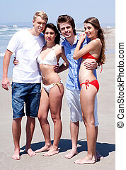 Four young adults standing on beach in swim wear