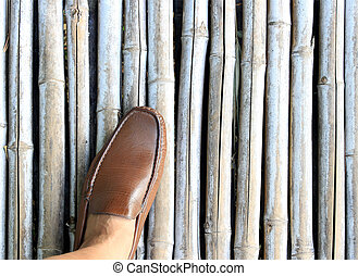 leg in brown shoe on bamboo wood background