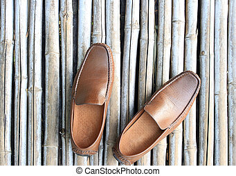 Brown shoe on bamboo wood background