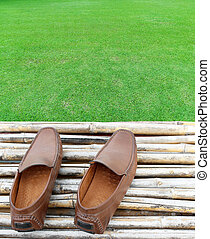 Brown shoes on bamboo wood and green grass field background