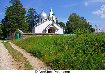 White orthodox temple on the green meadow