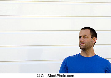 Squinting man in a blue shirt and white background.