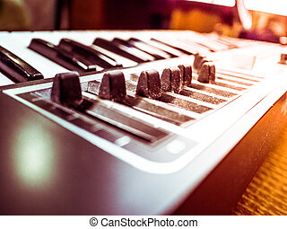 Keyboard of a synthesizer with sliders Closeup of musical...