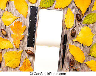 Closeup of notebook, ruler and pen, decorated with autumn yellow leaves and acorns. Top view, flat lay