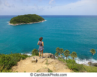 Woman looks on panoramic landscape from a rock. Amazing blue green sea and sunny day with island