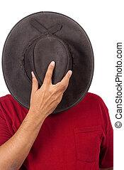 Hiding - A man covers his head with a cowboy hat - in hiding