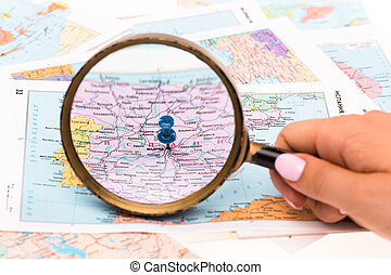 The female hand with magnifying glass on map