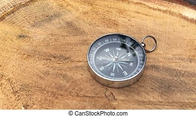 Human hand putting on a stump metal compass determines the...