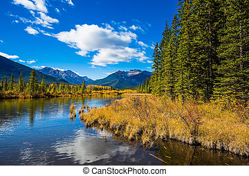 The shallow lake Vermilion among mountains - Day in the...