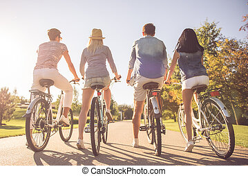 Friends cycling in park - Back view of beautiful stylish...