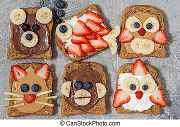 Funny animal faces toasts with spreads, banana, strawberry...