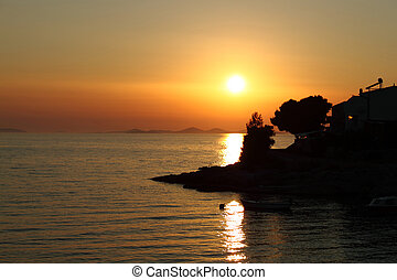 Romantic sunset with silhouette of coast