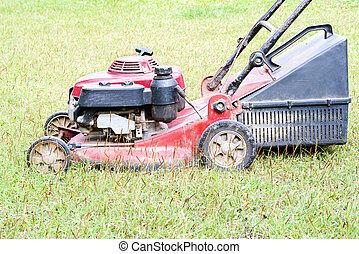 lawnmower - Old lawnmower stop on green grass in backyard.