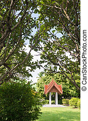 Belltower in a public temple, surrounded by green trees.