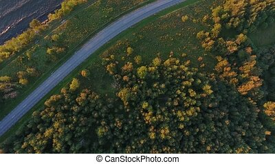 aerial view to cliff, sea and car driving on road