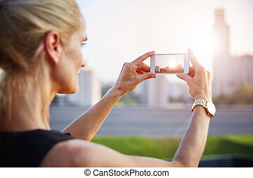Cityscape in smartphone - Portrait of mature woman taking a...