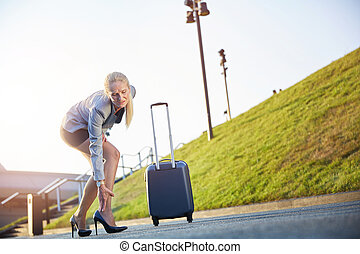 Businesswoman suffering from leg sore on business trip.