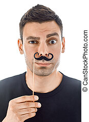 Young man with paper moustaches making faces isolated on...