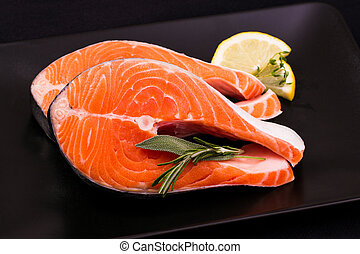Two delicious raw salmon slice with spices on black plate