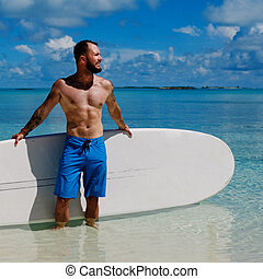 Man with Stand Up Paddle Board on the beach in Bahamas.