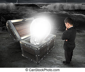 Man looking at bright light bulb in treasure chest