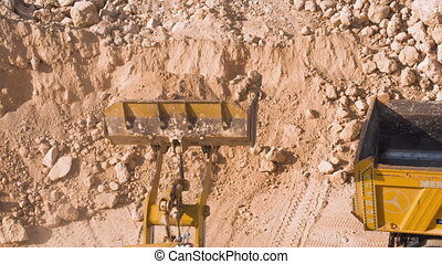 Dump truck being loaded with soil by shovel Construction...