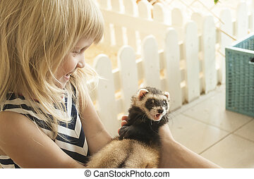 Little girl is taking a ferret in her arms
