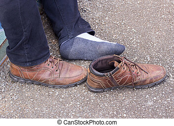 Men legs and old brown leather shoes on cement floor. Pair...