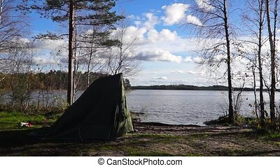 Oldschool tent rising up in the wild forest near lake in...