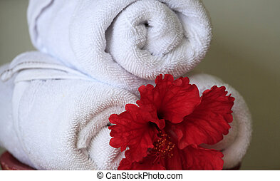 White rolled up towel with red flowers