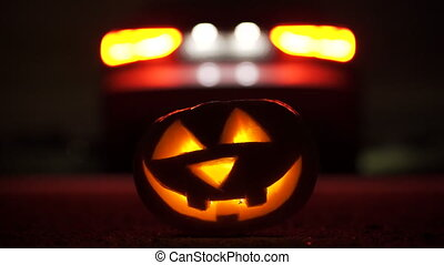 Jack o'lantern illuminated by headlights