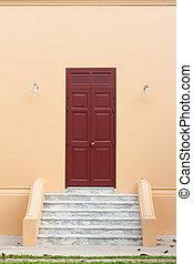 wooden brown door on orange wall - Ancient wooden brown door...