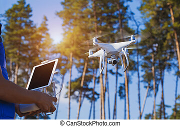 Flying the copter in the forest Remote control in a man's...