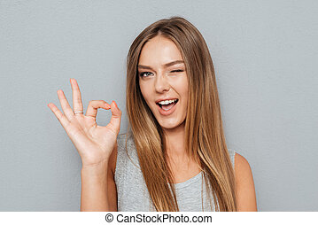 Happy young woman showing ok sign with fingers isolated -...