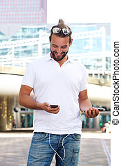 Smiling man holding cellphone and power bank