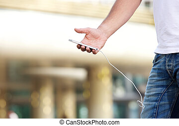 Man holding mobile phone with charging wire attached