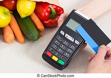 Hand of senior woman using payment terminal with contactless...