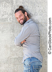 Smiling man leaning against wall with arms crossed