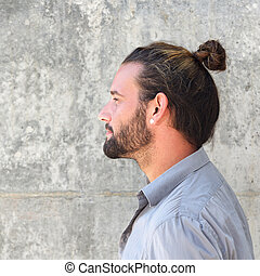 Side portrait of serious man with beard and hair bun - Close...