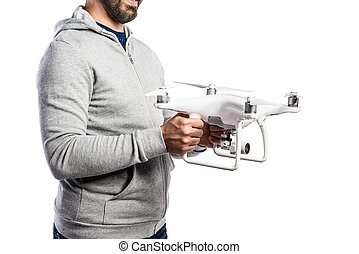 Unrecognizable man holding drone. Studio shot, isolated -...