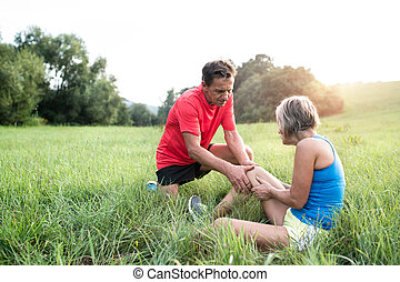 Senior runners in green field. Woman with injured knee. -...