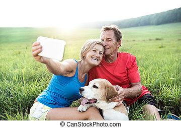 Senior runners with dog resting, taking selfie Sunny nature...