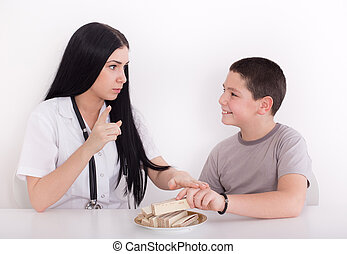 Doctor forbidding boy to eat sweets - Young female...