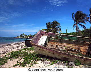 wooden fishing boat rotting on beach with hotel in...