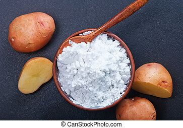 potato starch in bowl and on a table