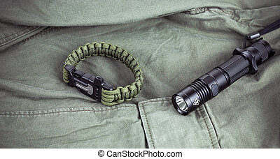 Military paracord bracelet and tactical torch on army-green...