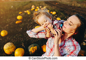 mother playing with her daughter on a field with pumpkins,...