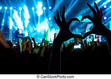Festival crowd raising hands in music concert front of...