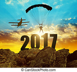 Concept New Year 2017 - Silhouette skydiver parachutist...