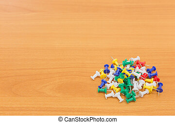 Colorful push pins on wooden background. with copy space
